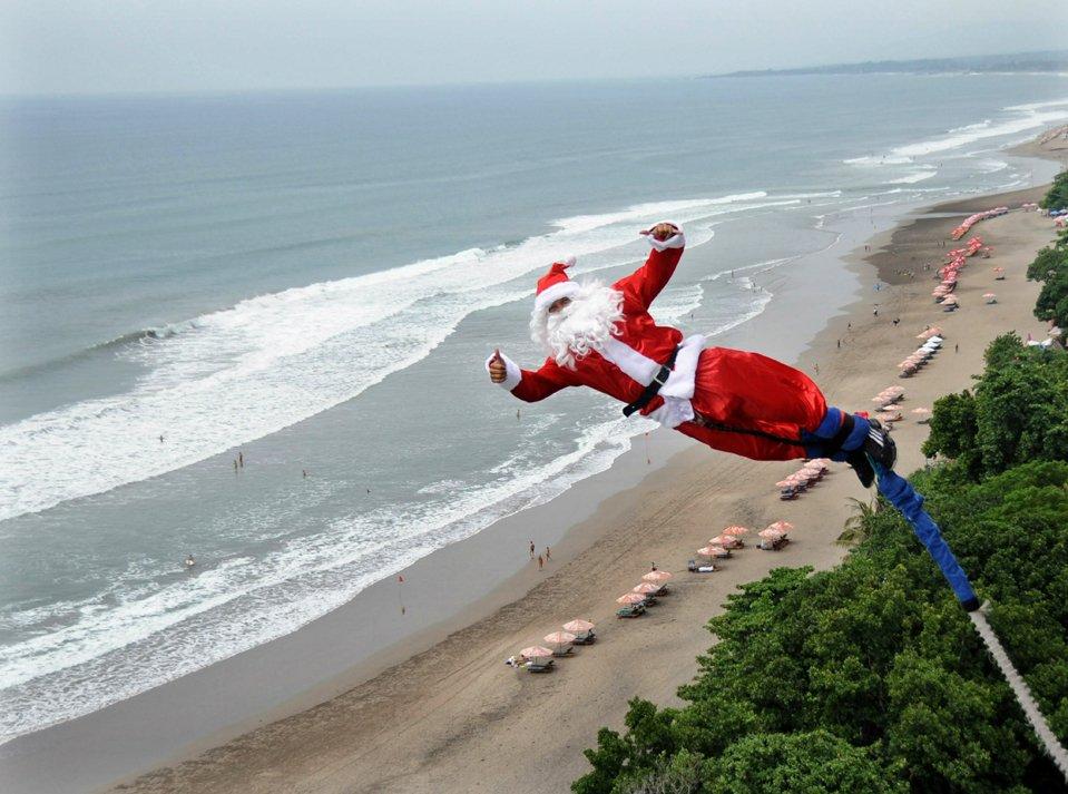 Санта Клаус прыгает на «тарзанке» в на пляже в Индонезии.