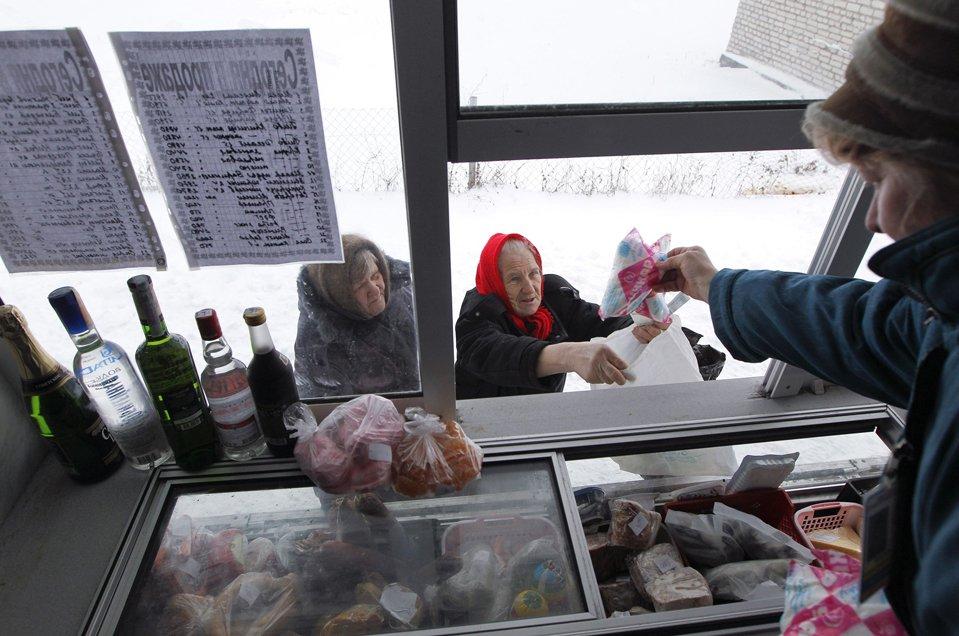 Люди покупают продукты с передвижного магазинчика в деревне Петковичи, Беларусия