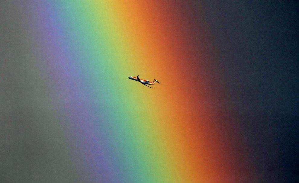 Самолет на фоне радуги над Средиземным морем