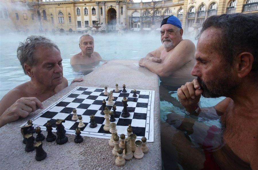 Люди играют в шахматы зимним утром в термальном комплексе Будапешта