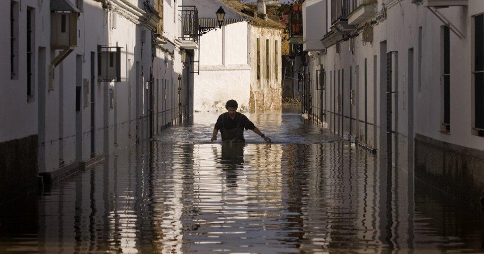 Человек идет по затопленной улице в Лора-дель-Рио