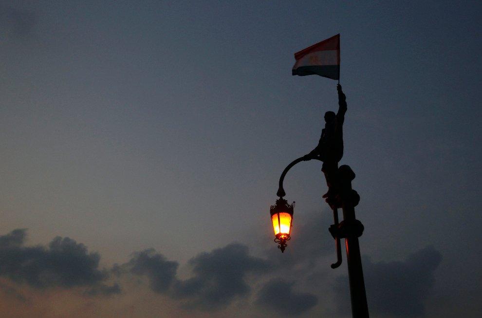 Один из протестующих машет национальном флагом на фонарном столбе