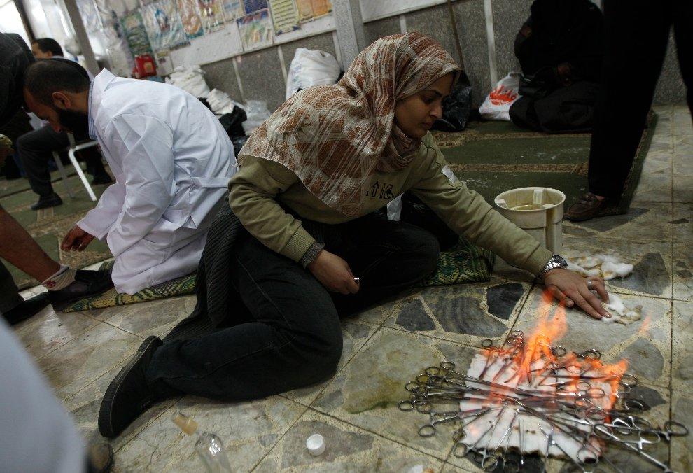 Женщина стерилизует ножницы, а врач оказывает помощь раненым в мечети Каира