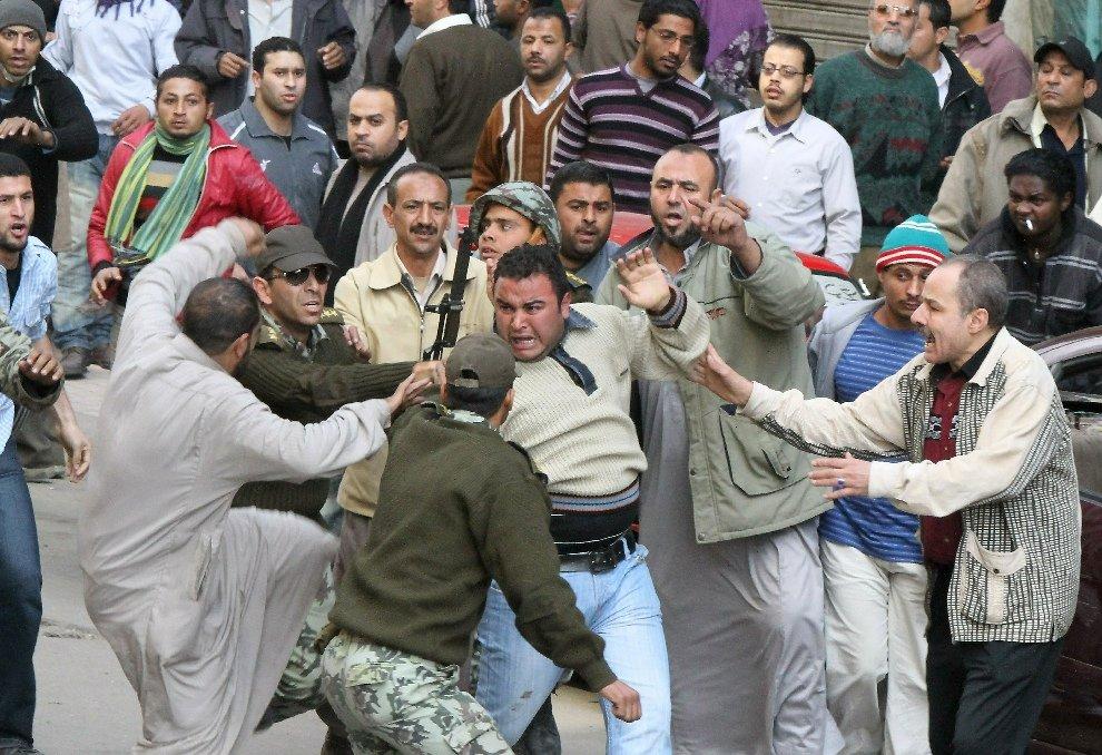 Египетские солдаты пытаются защитить человека от разгневанных демонстрантов