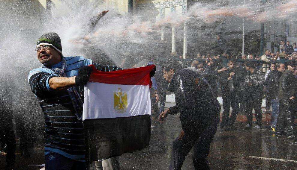Протестующий держит египетский флаг и уклоняется полицейских водометов в ходе столкновений в Каире