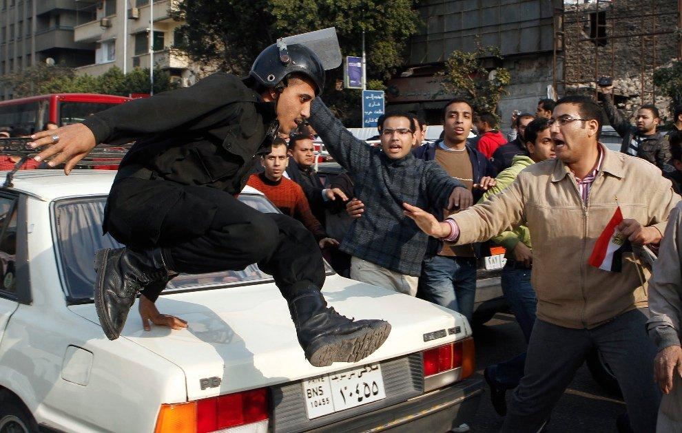 Полицейский перепрыгивает через машину в сторону к антиправительственной демонстрации