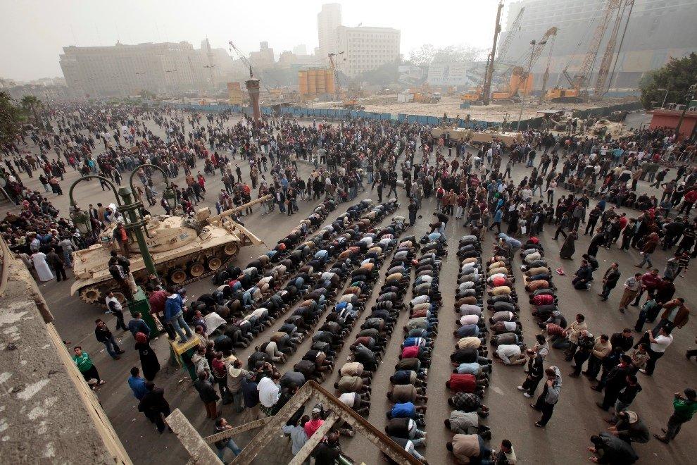 Протестующие молятся рядом с египетской танковой армией на площади Освобождения в Каире