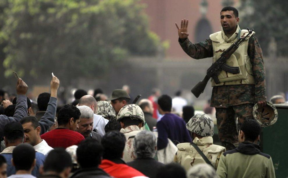 Солдат регулирует движение демонстрантов, прибывающих на площадь Освобождения в Каире