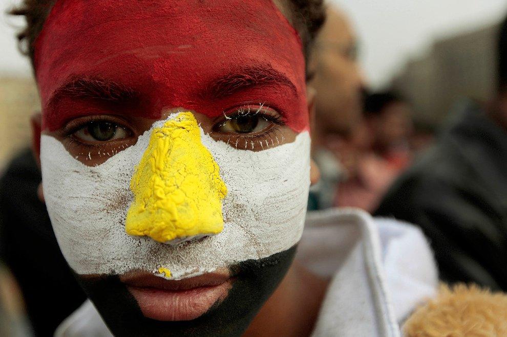 Лицо мальчика раскрашено в цвета египетского флага