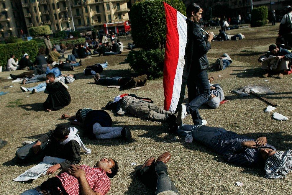 После нескольких дней протеста, некоторые измученные египтяне отдыхают на траве на площади Освобождения в Каире