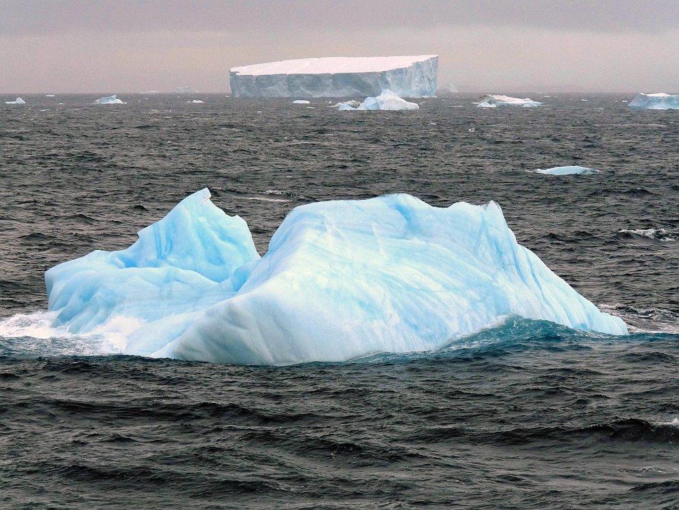 Маленький голубой айсберг и большой белый айсберг