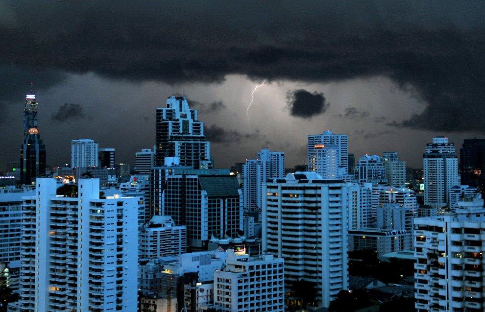 Молния освещает небо и здания в Бангкоке