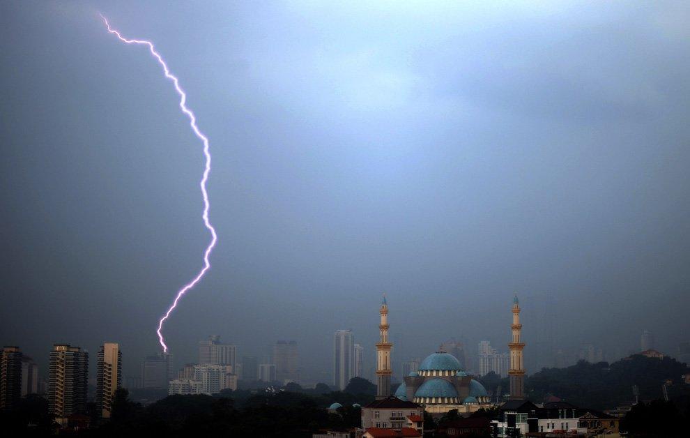 Молния пронзает небо недалеко от мечети в Куала-Лумпуре