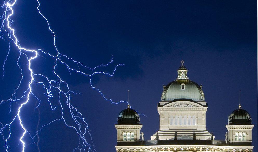 Молния освещает небо во время грозы над Федеральным дворцом в Берне, Швейцария
