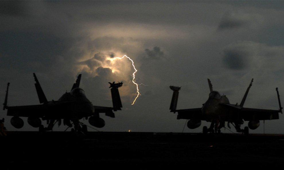Разряды молнии за двумя палубными истребителями-бомбардировщиками F/A-18C Hornet