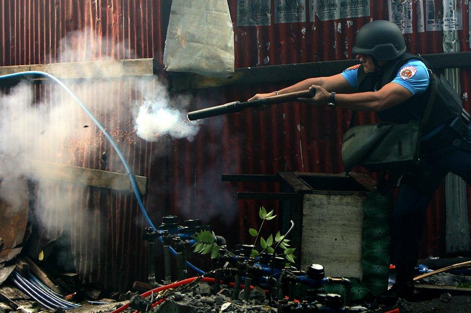Офицер полиции применяет слезоточивый газ