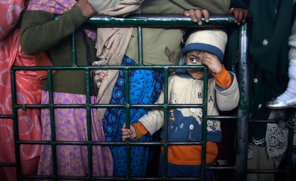 Мальчик стоит со своей мамой в очереди за продовольствием