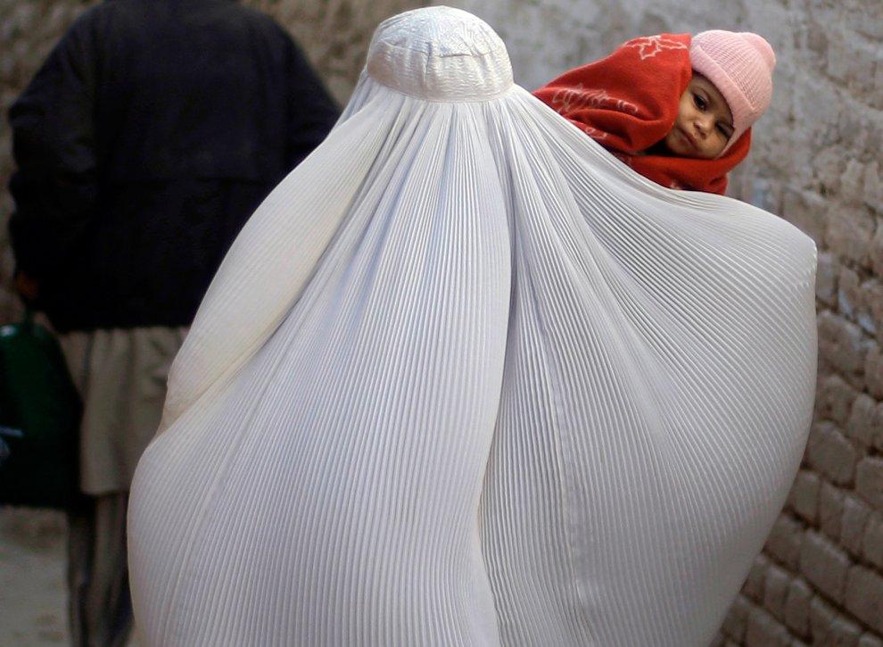 Мама со своей маленькой дочкой в трущобах на окраине Исламабада
