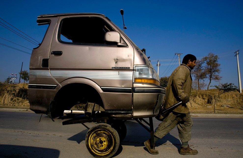 Рабочий на дороге использует переднюю часть кузова микроавтобуса как тачку