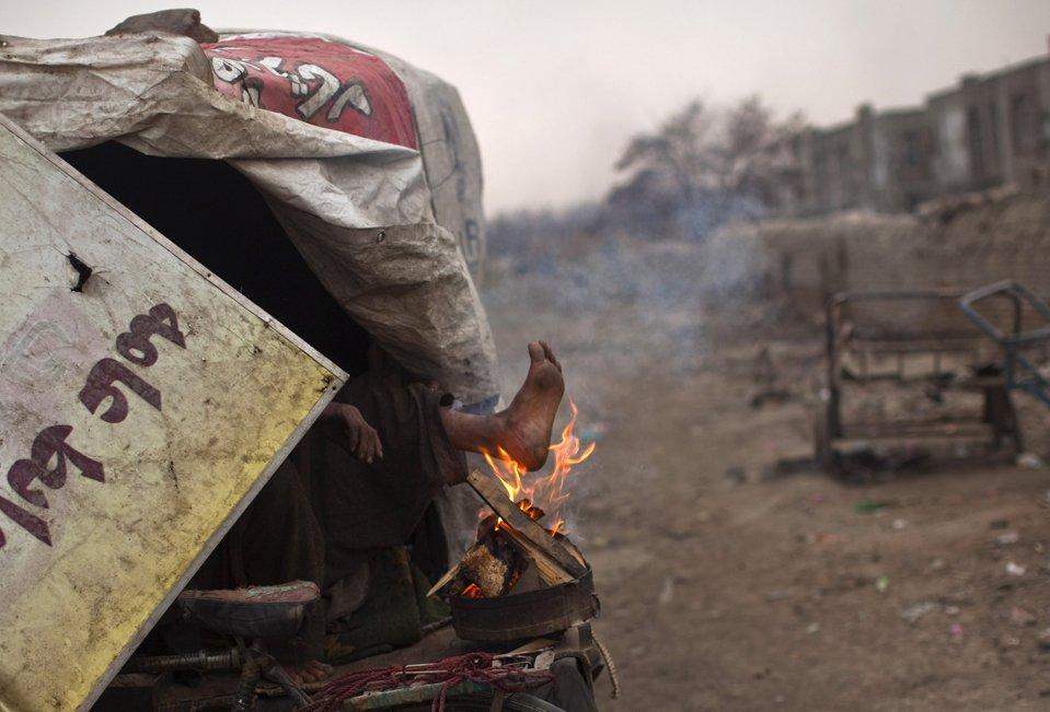 Бездомный греет ноги от огня, Кабул, Афганистан