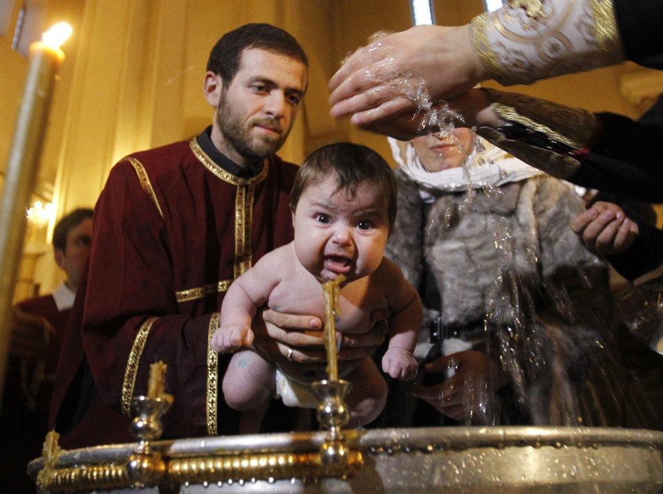 Ребенка крестят во время христианского праздника в Тбилиси