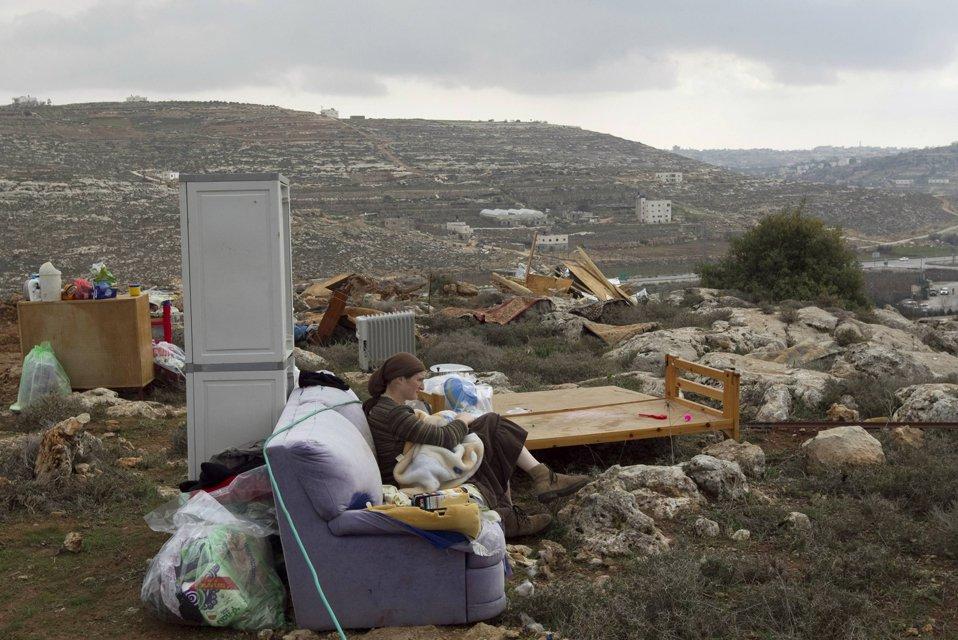Женщина с ребенком и своими вещами сидит на месте своего бывшего жилища