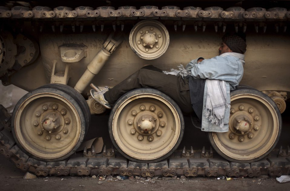 Участник акции протеста против президента Хосни Мубарака спит на колесах танка