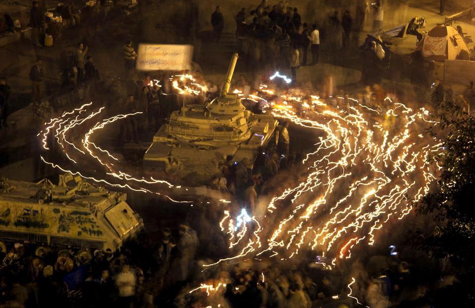 Демонстранты ходят вокруг танка на площади Тахрир в Каире со свечами