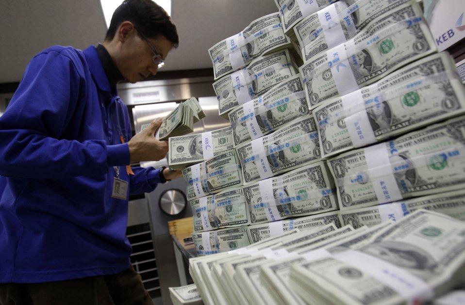 Банковский служащий сортирует пачки с американской валютой