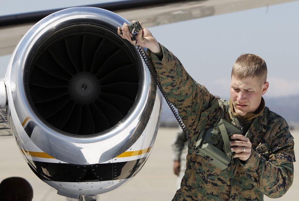 Американский солдат проверяет уровень радиации у самолета в аэропорту Сендай
