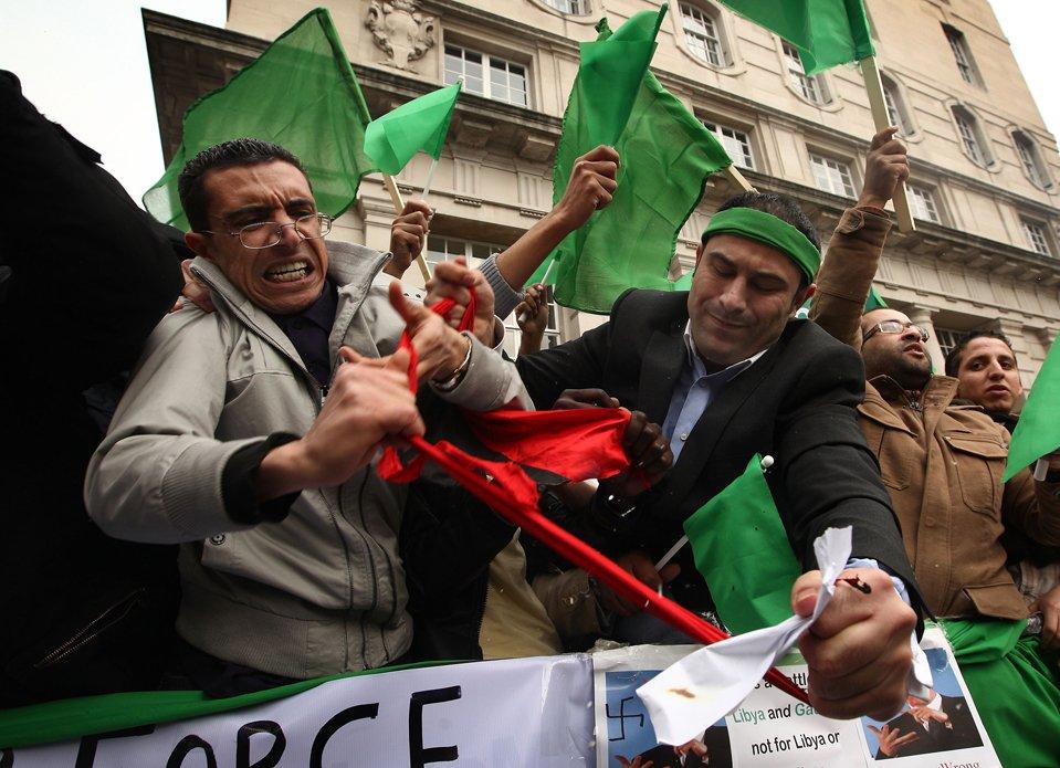 Сторонники Муамара Каддафи рвут флаг, отобранный у мятежников