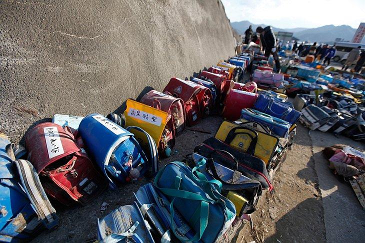 Школьные ранцы лежат возле разрушенной цунами начальной школы в городе Исиномаки в префектуре Мияги на