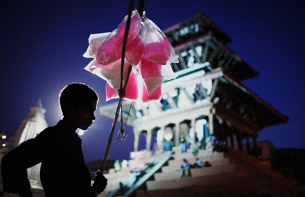 Мальчик-продавец конфет и сахарной ваты на улице в Катманду