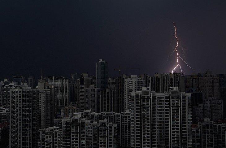 Удар молнии над темными зданиями в центре Шанхая во время шторма 15 августа 2012