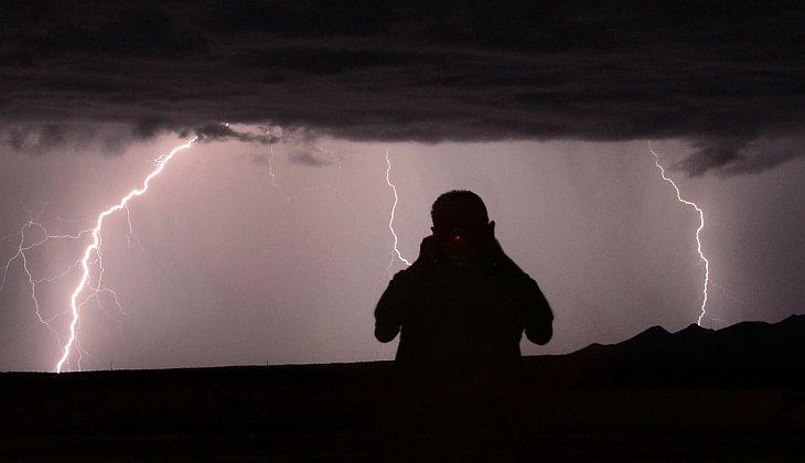 Силуэт фотографа-охотника за бурями Mike Meadows на фоне молний