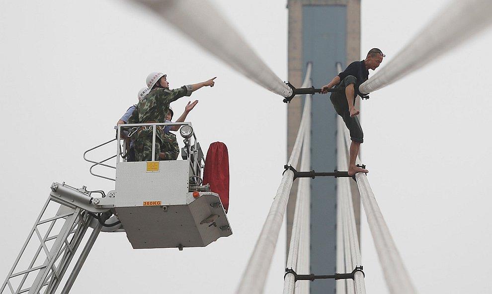 Спасатели пытаются остановить самоубийцу на вершине моста через реку Янцзы в городе Ухань