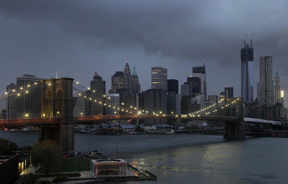 Огни на Бруклинском мосту исправно работают, на фоне нижнего Манхэттена, который остался без электричества