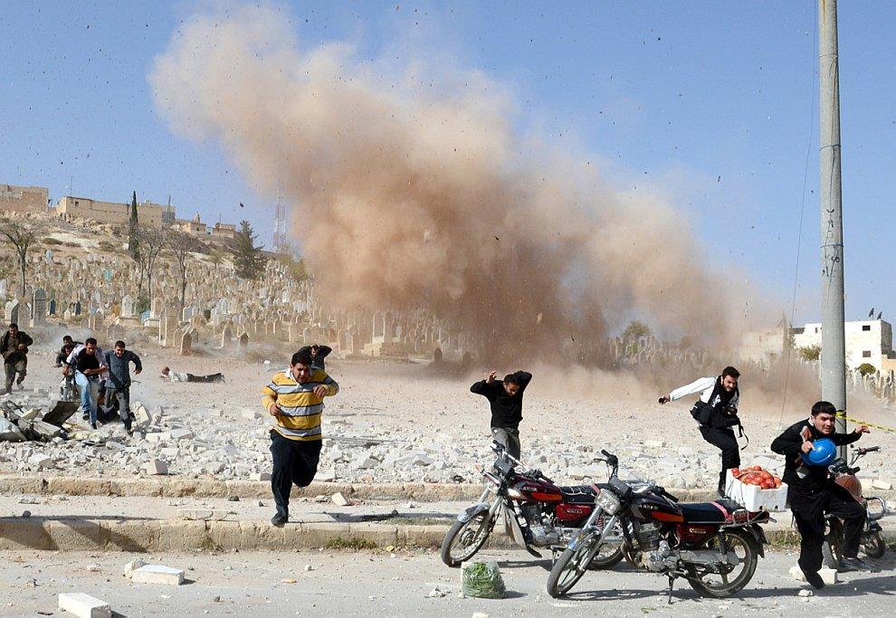 Гражданские пытаются скрыться от взрыва бомбы