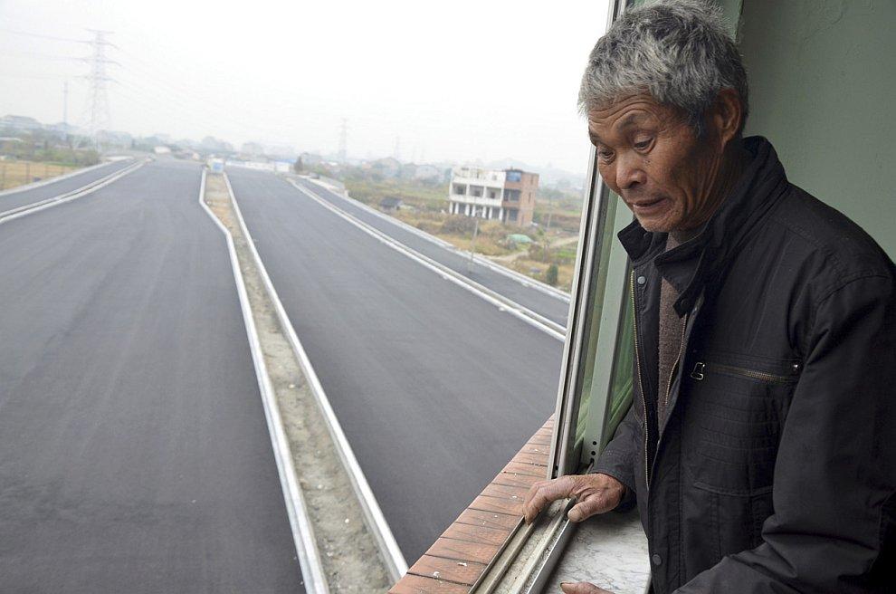 Хозяин Чжэцзян Лю Баоген смотрит на только что построенное скоростное шоссе, которое со всех сторон огибает его здание