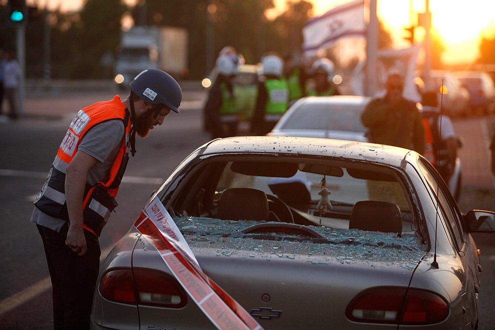 Израильские спасатели осматривают автомобиль после ракетного удара с территории сектора Газа