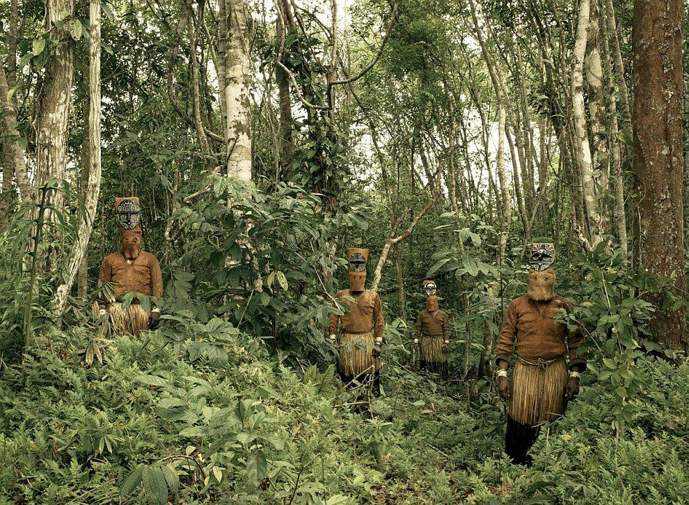 Посреди джунглей колумбийской Амазонии стоят индейцы, одетые в традиционные племенные одежды
