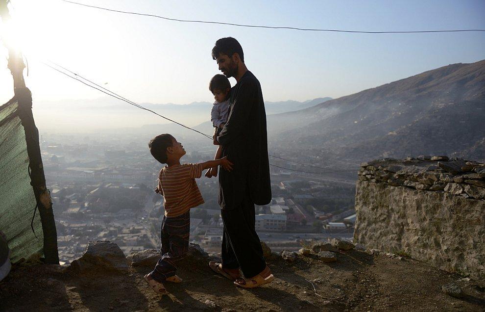 Афганец на склоне холма рядом со своим домом в Кабуле