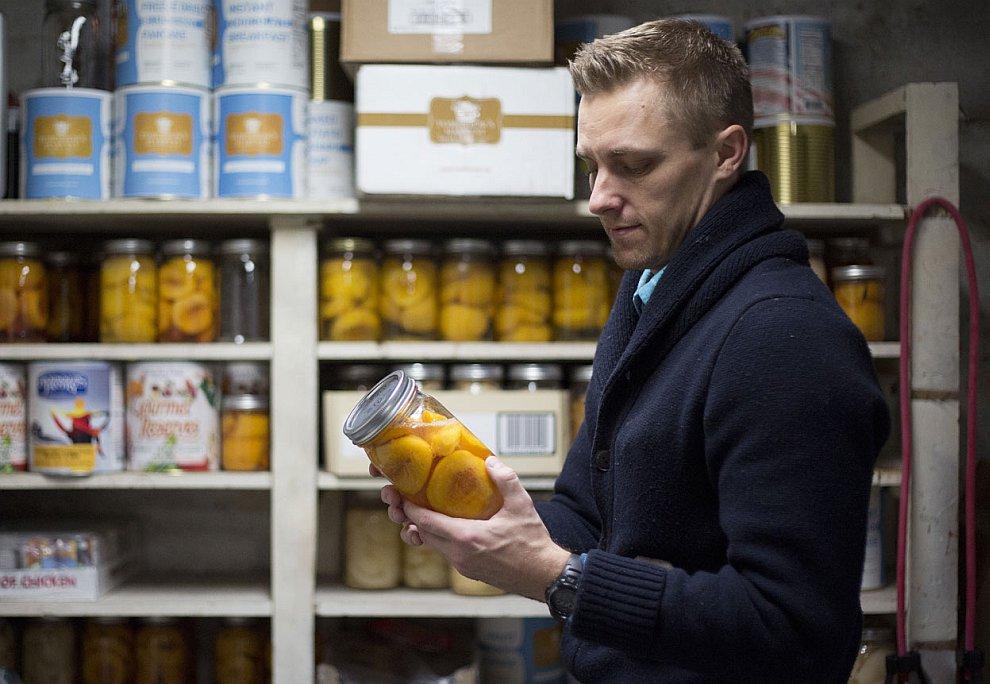 Житель одного из городков в штате Юта проверяет запасы продовольствия в подвале своего дома