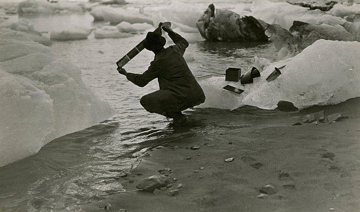 Фотограф на Аляске моет пленку со снимками в талой воде
