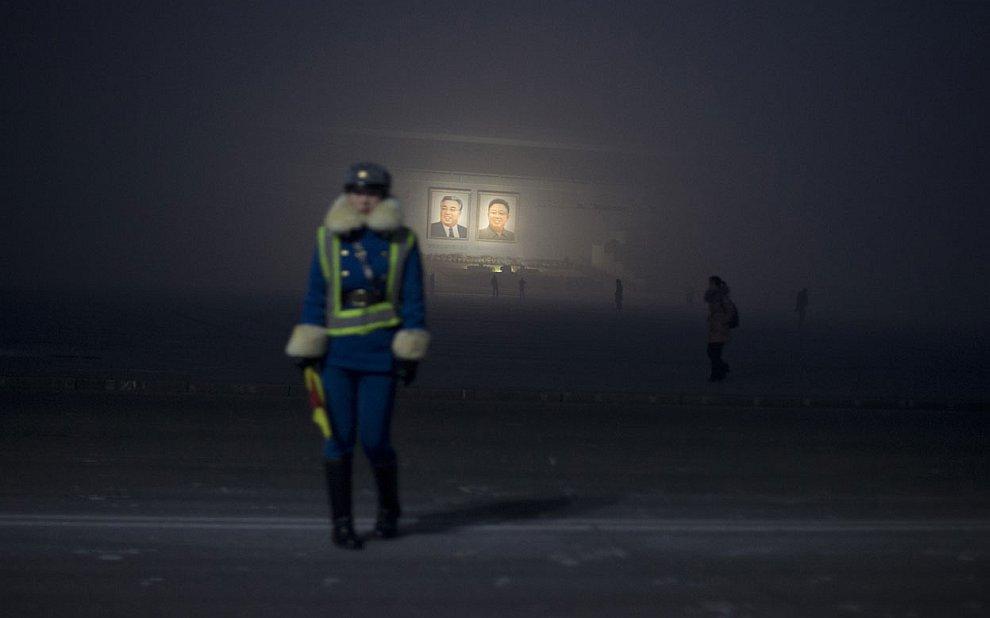А посреди пустынных улиц, на фоне портретов покойных лидеров Ким Ир Сена и Ким Чен Ира стоят регулировщицы, Пхеньян