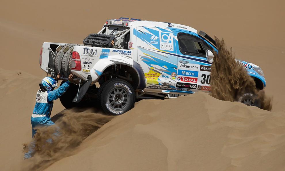 Аргентинский экипаж вытаскивают пикап, застрявший на дюне во время 6-го этапа Дакар