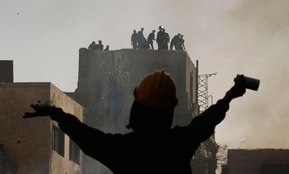 Участник беспорядков и полицейские на крыше здания