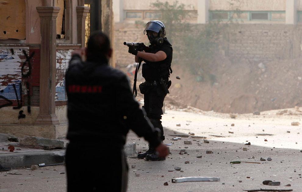 Протестующий, полицейский с оружием, стреляющим снарядами с газом и куча камней на земле, которыми забрасывали полицию