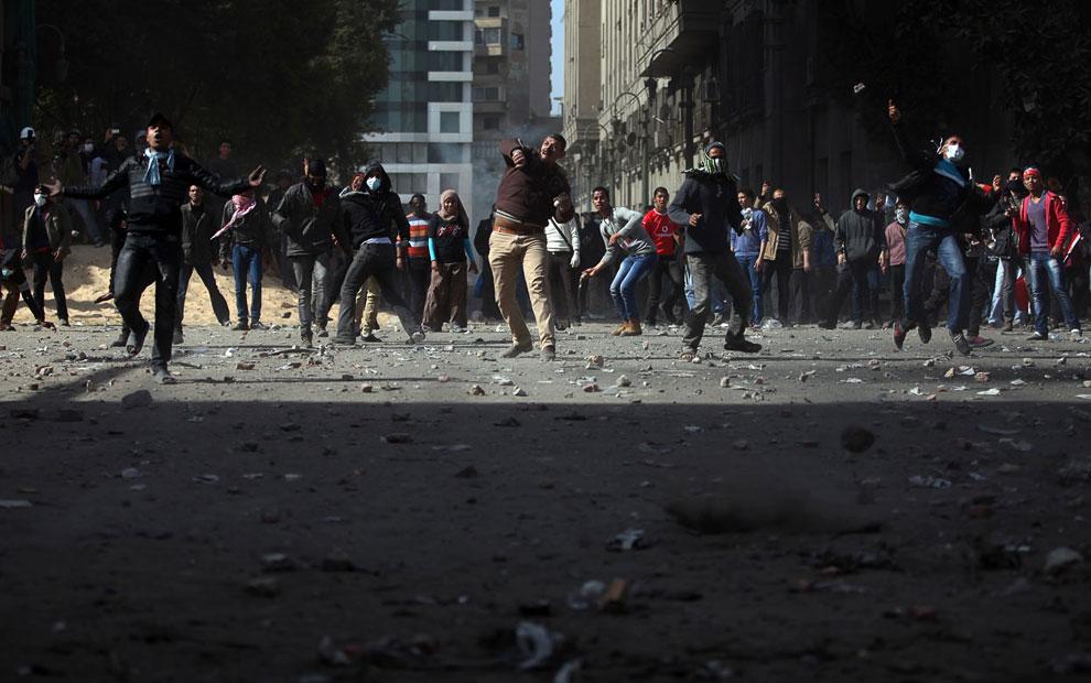 Египетские протестующие бросают камни в ОМОН возле площади Тахрир
