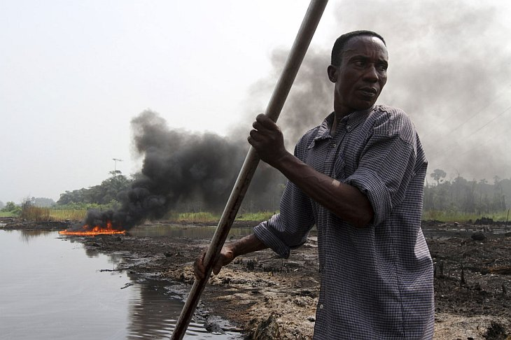 Плывет на каноэ рядом с местом взрыва нефтепровода, из которого люди пытались украсть нефть